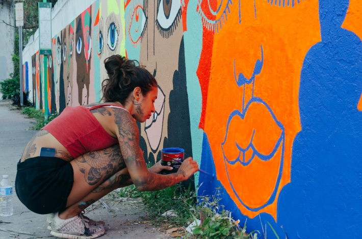 Artist Marilyn Rondon painting a mural